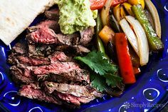 Classic Tex Mex fajitas recipe, made with strips of skirt steak, onions and bell peppers, and served sizzling hot with fresh tortillas, guacamole, sour cream, and salsa.