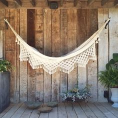 Covered room in the shade with a white, lace-trimmed hammock