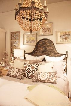 Rustic and romantic bedroom with vintage chandelier, wood headboard & embroidered pillows