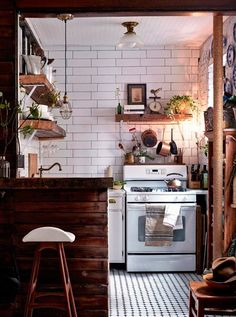 This pint-sized kitchen goes to show you needn't be nervous about mixing up your materials in a small space. Keep to a neutral colour palette and go to town with reclaimed wood, ceramic metro tiles, copper – anything goes. The use of cladding will also give your kitchen a cosy cabin feel, as supposed to just being plain old small. A handsome dish, indeed. #refinery29 http://www.refinery29.uk/small-kitchen-ideas-interiors-tiles#slide-1