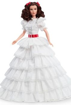 "The Gone With The Wind™ Scarlett O'Hara™ portrait doll wears a recreation of the dress worn in the movie's opening scene. Known as the ""ruffle dress"" and the ""prayer dress,"" the gown features 6 cascading tiered ruffles made from fine-woven Dobby cotton, edged with lace. The upper bodice features large extended sleeves, lace detail + tiny white buttons. A bold red belt accentuates the waist complemented by two red hair bows. Sculpted in Vivian Leigh's likeness. A white cameo finishes the…"