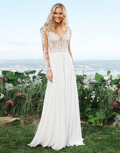 Feel dreamy in this feminine chiffon A-line gown with an illusion V-neckline, lace appliqués on the sleeves and sheer back, and a dropped waistline. This gown is completed with a chapel length train. https://www.lillianwest.com/lillian_west/6422