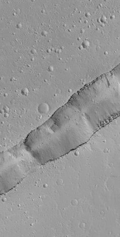 Labeatis Trough-This Mars Global Surveyor (MGS) Mars Orbiter Camera (MOC) image shows a portion of a trough cutting across a dust-covered plain in the Labeatis Fossae region of Mars. Boulders derived from the layered exposures near the top of the trough walls are resting on the floor, and in some locations, the sloping sidewalls of the dusty trough. MGS MOC Release No. MOC2-1511, 2 July 2006  Credits: NASA/JPL/Malin Space Science Systems