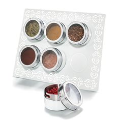 """Keep spices handy with this magnetic board/container set that stands up on the table or hangs on a wall. The white, magnetic metal rack holds 6 spice containers (containers included). Containers feature a twist off lid with a clear middle to see the inside easily.FEATURES• Rack: 9.75"""" x 8""""• Spice containers (set of 6): 2.5"""" x 1.5""""• Containers are white/silver• Rack has a white pattern trim around borderMATERIALS• Iron Rack• Stainless steel containersCARE• W..."""
