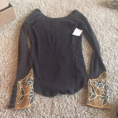 NWT Free people BALI BABE thermal NWT . Color is not as black as advertised in stock photos. It's more vintagey .. More grey toned black if that makes sense .  Long sleeve thermal boasts intricate detailing at the cuff for eye-catching style. Wide round neckline. Open back. Embroidered cuffs flaunt a button-snap feature. Curved hemline. 57% cotton, 38% polyester, 5% spandex;Trim: 100% cotton. Machine wash cold, flat dry. Imported. Measurements Length: 26 in Free People Tops