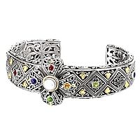 This multicolor gemstone, silver, and 18K yellow gold cuff makes a great addition to any outfit! style 610-189