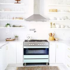 Chic kitchen features a stainless steel hood over a blue stove flanked by stacked floating shelves, Beautiful kitchen boasts white cabinets adorned with brass hardware and sleek white ocuntertops alongside a pink rug.