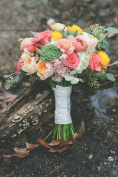 Bouquet filled with succulents and flowers of coral and yellow
