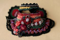 This unique crochet cuff is made in the colors of a traditional Bulgarian rug - mainly black combined with dark red fibers, yellow, green, gray,