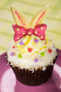 Disney Parks pineapple-coconut Easter cupcake March 18 – March 31: Almost too pretty to eat (but not quite) is the pineapple-coconut cupcake for Easter, yellow cake with white buttercream, coconut shavings and colorful confetti, with a pair of adorable, white chocolate bunny ears and pink polka-dot bowtie perched on top.