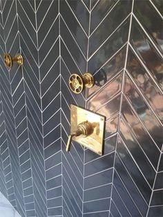 black chevron subway tile and brass shower fixtures.