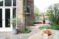 Een driehoekig perceel tegen een kerkmuur werd omgetoverd tot een stoere stadstuin met 2 terrassen, een pizzaoven, reuzenschommel, kruidentuin, fietsenstalling en zelfs 'een bosje', voor een buitengevoel midden in de stad. De bewoners wilden een weelderige beplanting. Stoere betontegels zijn gecombineerd met oud Hollandse klinkers die passen bij de sfeer van de kerk.