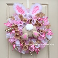 This adorable Easter bunny wreath will be perfect for your door this Spring! This wreath measures 24 in diameter with a depth of 8. It is constructed out of metallic white and pink deco mesh and burlap deco mesh. It is adorned with pink and tan polka dot ribbons. In the center