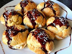 7 cream puffs glazed with chocolte and topped with desiccated coconut on a white plate