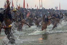 Naga Sadhus run naked into the water at Sangam, during the royal bath on Makar Sankranti at the start of the Maha Kumbh Mela in Allahabad, on January 14, 2013. (AP Photo/Kevin Frayer)