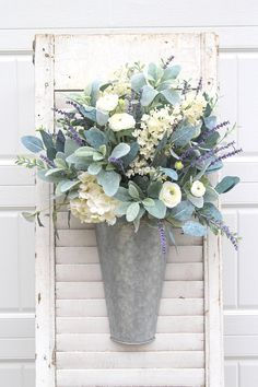 Farmhouse Door/Wall Hanger at its best. Anything with Lavender and Lambs Ear is always super popular. Add paniculata hydrangeas and creamy white ranunculus with flocked boxwood and you have the perfect Farmhouse piece. The galvanized door hanger has a hook on the back for easy hanging.