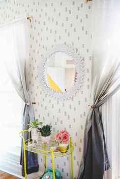 Pulling everything together: brush-stroke walls in light grey.  Curtains that gradually seep into gray and a bright, neon yellow bar cart.  --LYC