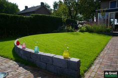 Glooiend gazon, stapelblokken en hoogte verschil in de moderne tuin met een ronde vorm.
