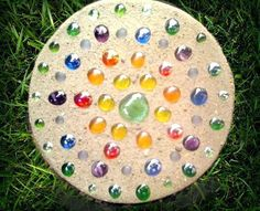 Simple and fun concrete steppingstone adorned with colorful glass gems, adds beauty to any landscape or garden! By Artist Jenny Russ