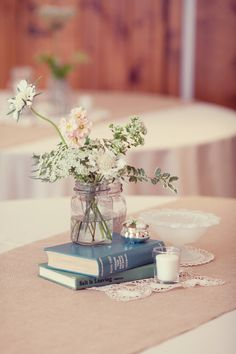centerpiece flowers in stacked jars, doily, burlap runner, I love the books!