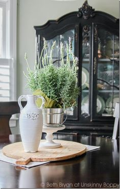 Kitchen table decor on a bread board. So pretty! Lavender in a bucket with a white vase. Simple and gorgeous.