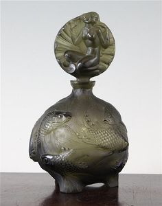 Art Deco Bohemian olive green glass 'fish' perfume bottle moulded in relief with ornamental carp and stopper with nude female and shells