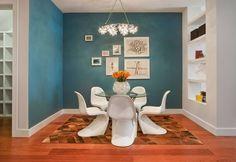 A tonalidade próxima do azul petróleo funciona bem com o piso amadeirado, de nuance alaranjada. As cores, complementares entre si, ressaltam-se mutuamente na base do contraste.O fato de terem sido duas, e não uma, as paredes pintadas, garantiu mais unidade ao espaço.