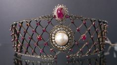 At least three tiaras have found themselves caught up in the wrangling between Imelda Marcos and the Philippine government. This is one such piece once owned by the former first lady. A large lattice of rubies and diamonds, centered on a pearl surrounded with diamonds, with a cabochon ruby above it.
