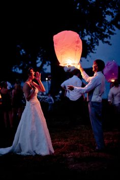 i love this image of delight as a bride watches her husband release a floating lantern