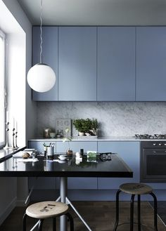 Each element in this kitchen stands out, from the slate blue kitchen cabinets, to the unique metals legs of the dining table and the numbered kitchen stools.