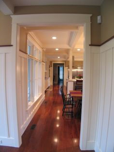 Love the warm wood floors, white wainscoting and the open view into the rooms.