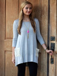 This simple grey t-shirt style tunic is perfect with leggings and boots! Such a cute simple tunic with a hint of lace and pocket on both sides in the front. The crochet details and simple buttons down the back add a sweet little detail to this tunic. Wear it for a day of shopping or to a fun Mari Gras parade. Our model is wearing a small. 95% Rayon / 5% Spandex