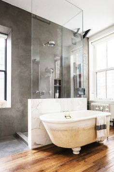 Bathroom with a concrete shower, wood floors, and a floating tub