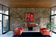 Serra do Rio de Janeiro. Em uma extremidade, a sala acolhe a mesa de jantar e, na outra, o estar com lareira. O ambiente abre-se para a frente e os fundos da casa, integrado ao jardim por portas de correr envidraçadas, fixadas em finas esquadrias metálicas. Casa Cavanelas, de Oscar Niemeyer e Roberto Burle Marx.