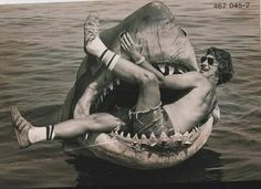 Steven Spielberg sits in the mechanical shark used in JAWS