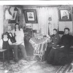 """Thomas A Hillary (2nd left) and his Wife Elizabeth Osborne Hillary (far right) in their living room around 1896, Cornwith, Iowa. Children: CliffordHillary, far left (still in his """"skirts"""") Betha Hillary, centre Alfred Hillary, 2nd from right Pictures on the wall (left to right) are belived to be Mary Hillary (died aged 6) Thomas Hillary (1818 - 1860) Faith Hillary, nee Hodsgon (1818 - 1904)"""