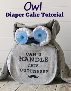 Owl Diaper Cake Tutorial - This sweet owl diaper cake makes a cute baby shower centerpiece. A bib, receiving blanket, some diapers, two binkies, and a knit bootie are all the supplies you need. The mustache print is perfect for a boy!