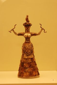 Minoan Snake Goddess. The goddess, or priestess, is depicted with exposed breasts and wearing a rich garment. Her bared breasts suggest her capacity as fertility goddess, 16th c BCE