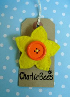 A bright daffodil felt brooch. Made with 100% wool felt. Hand-sewn and with a wooden button in the centre of the flower. Brooch back as shown