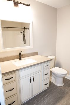 Bathroom vanity set-up using Yorktowne cabinetry in the Crowley door style with Divinity White paint and a Burnt Sienna highlight.