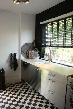 Zwarte horizontale houten jalouzie, geblokte vloertegel, rvs keuken, wit werkblad, schoolbordverf.