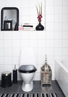 black toilet seat + black and white rug + silver light