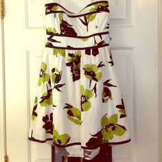 Strapless White Flowered Dress size 9 White background dress with green and Black flower pattern. Has a zipper in the back along with a ribbon tot tie. Size 9 but can fit size 7 as well. Speechless Dresses
