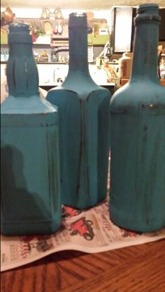 Whiskey bottles  spray painted black then hand painted turquoise and sanded down for the vintage look (agr )