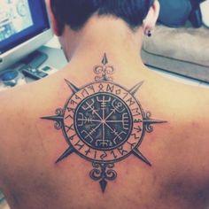 hier ist ein mann mit einem großen, schwarzen, modernen tattoo mit einem schwarzen kompass auf dem rücken und ohrringen