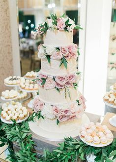 How beautiful is this four tier wedding cake decorated with fresh pink and white roses!
