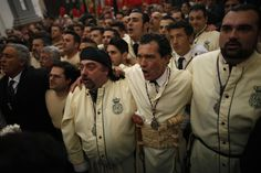"""Film actor and director Antonio Banderas, second right, sings a song to the Virgin inside a church as he takes part as a penitent in the """"Lagrimas and Favores"""" brotherhood in a Palm Sunday procession in Malaga on March 24, 2013."""