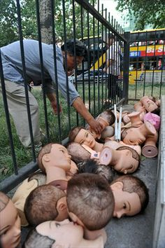 A man tries Saturday to retrieve one of the 40-plus mannequin heads that were found abandoned in a fenced area beside Chang'an Road in Xi'an, Shaanxi Province.