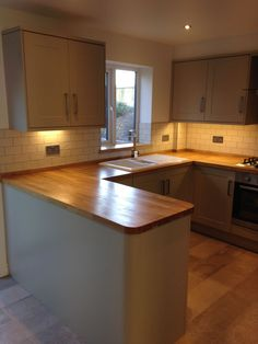 Burford grey, solid oak work tops and white crackle tiles