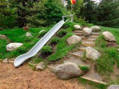 In this publicity photo provided by Natural Playgrounds Company, an embankment slide is built into a constructed hill at an elementary school as shown here in Glens Falls, N.Y. The embankment slide is safer than tower slides with ladders. Scattered boulders, random dirt steps, rough terrain, and varied plantings add to the rich textures and varied experiences on Natural Playgrounds. (AP Photo/Natural Playgrounds Company)